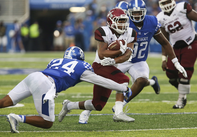 New Mexico State running back Xavier Hall, center, splits Kentucky defenders Blake McClain, left, and Alvonte Bell, right, in the second half of an NCAA college football game Saturday, Sept. 17, 2 ...