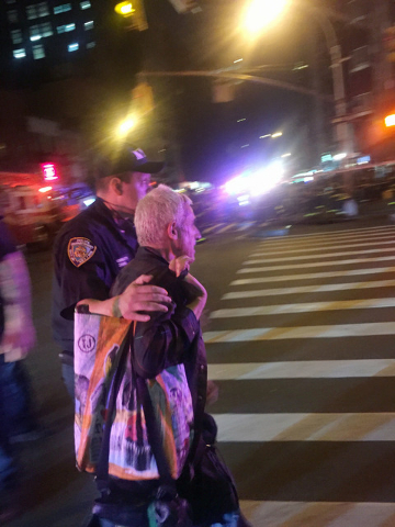 A police officer escorts an injured man away from the scene of a possible explosion on West 23rd Street in New York. Authorities said dozens suffered minor injuries. (Nico Maounis/Associated Press)