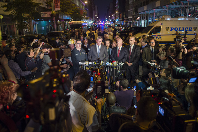 Mayor Bill de Blasio, center, and NYPD Chief of Department James O'Neill, center right, speak during a press conference near the scene of an apparent explosion on West 23rd street in Manhattan's C ...
