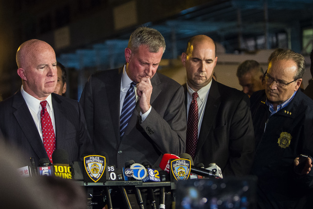 Mayor Bill de Blasio, center, and NYPD Chief of Department James O'Neill, left, react during a press conference near the scene of an explosion on West 23rd street in Manhattan's Chelsea neighborho ...