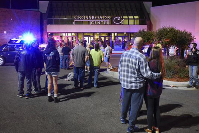 People stand near the entrance on the north side of Crossroads Center mall between Macy's and Target as officials investigate a reported multiple stabbing incident, Saturday, Sept. 17, 2016, in St ...