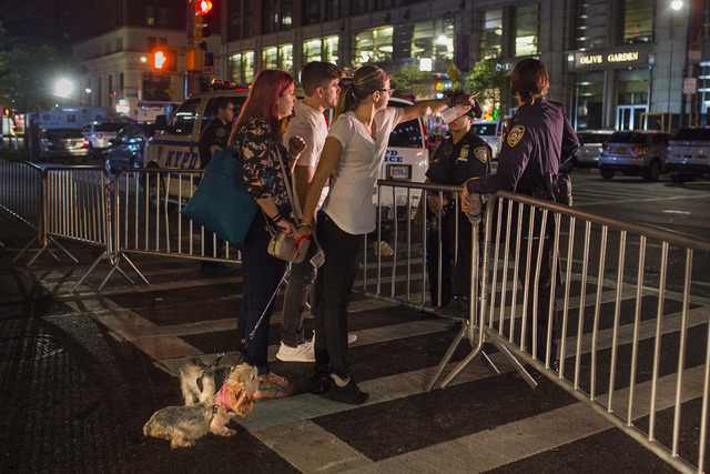 People try to access the area near the scene of an explosion on West 23rd Street and 6th Avenue in Manhattan's Chelsea neighborhood, in New York, early Sunday, Sept. 18, 2016.  (Andres Kudacki/Ass ...