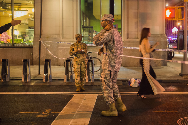 People try to access the area near the scene of an explosion on West 23rd Street and 6th Avenue as members of the military stand guard in Manhattan's Chelsea neighborhood, in New York, early Sunda ...