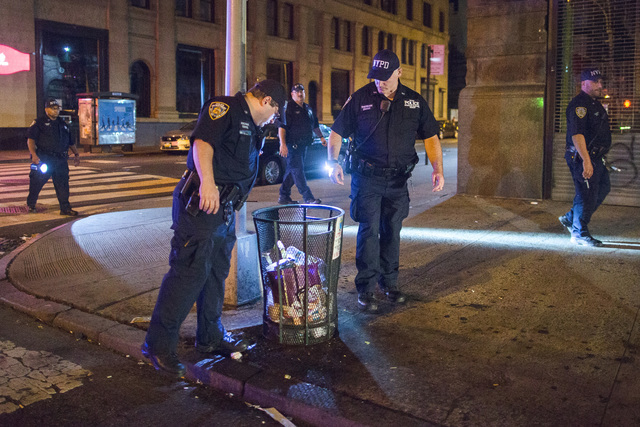 Police officers look for suspicious packages along Fifth Avenue near the scene of an explosion on West 23rd Street and 6th Avenue in Manhattan's Chelsea neighborhood in New York, early Sunday. (An ...