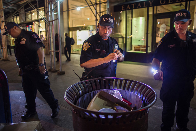 Police officers look for suspicious packages along Fifth Avenue near the scene of an explosion on West 23rd Street and 6th Avenue in Manhattan's Chelsea neighborhood. (Andres Kudacki/Associated Press)