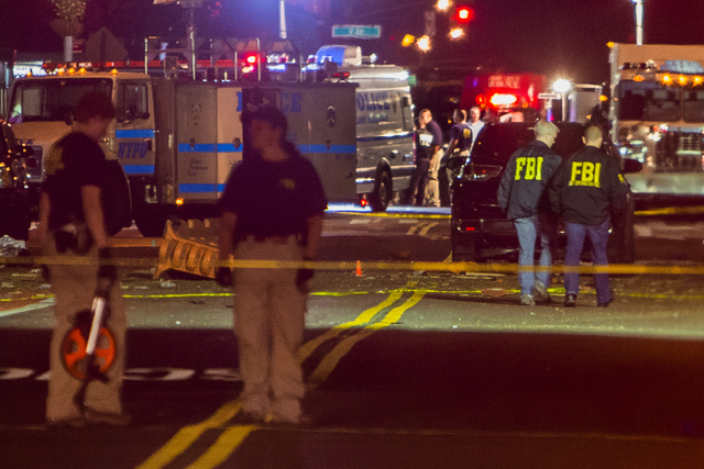 Members of the Federal Bureau of Investigation (FBI) carry on the investigations in the scene of an explosion on West 23rd Street and 6th Avenue in Manhattan's Chelsea neighborhood.  (Andres Kudac ...