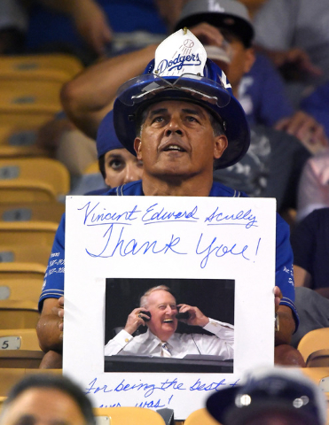 A fan holds up a picture of Hall of fame broadcaster Vin Scully prior a baseball game between the Los Angeles Dodgers and the San Francisco Giants, Tuesday, Sept. 20, 2016, in Los Angeles. (Mark J ...