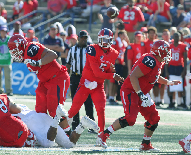 Fresno State's Chason Virgil passes against Tulsa defenders during the second half of an NCAA college football game in Fresno, Calif., Saturday, Sept. 24, 2016. (Gary Kazanjian/AP)