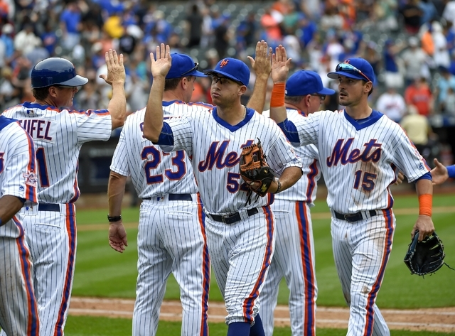 New York Mets'  T.J. Rivera (54) and Matt Reynolds (15) high five with teammates after the Mets beat the Minnesota Twins 3-2 in a baseball game, Sunday, Sept. 18, 2016, in New York. (Kathy Kmonice ...