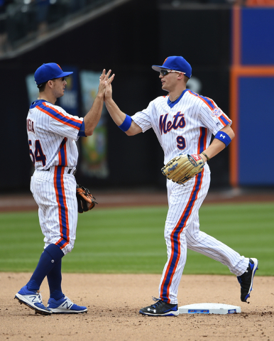 New York Mets second baseman T.J. Rivera (54) and left fielder Brandon Nimmo (9) celebrate their 3-2 win over the Minnesota Twins in a baseball game, Sunday, Sept. 18, 2016, in New York. (Kathy Km ...