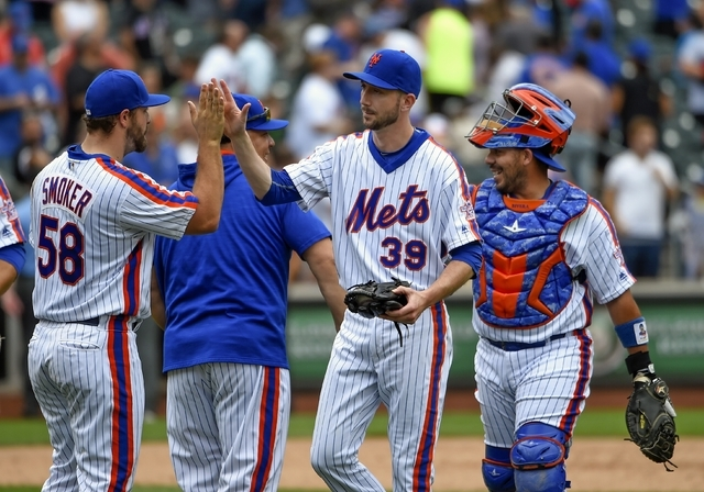 New York Mets relief pitcher Josh Smoker (58), relief pitcher Jerry Blevins (39),  starting pitcher Bartolo Colon (40) and catcher Rene Rivera celebrate their 3-2 2in over the Minnesota Twins in a ...