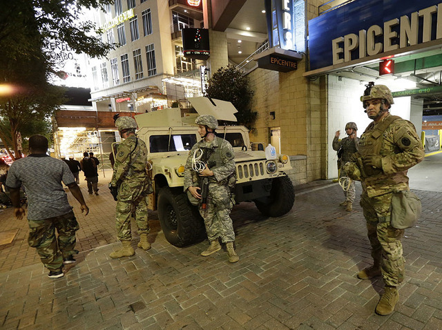 National Guardsman stand on the street in downtown Charlotte, N.C. on Thursday, Sept. 22, 2016. Charlotte police refused under mounting pressure Thursday to release video that could resolve wildly ...