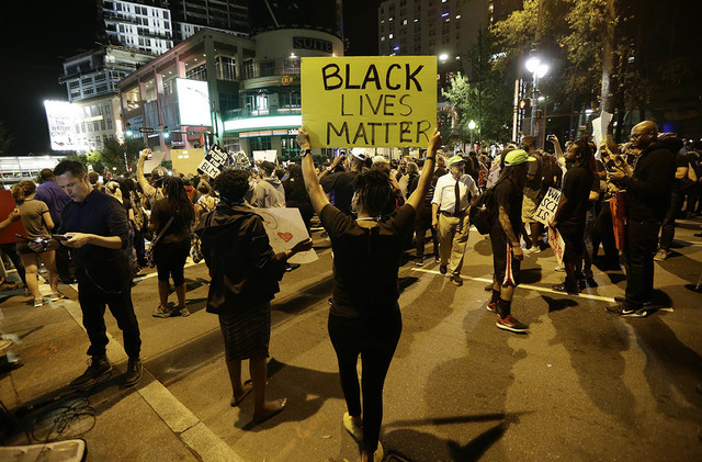 Protesters take to the streets of uptown during a peaceful march following Tuesday's police shooting of Keith Lamont Scott in Charlotte, N.C., Thursday, Sept. 22, 2016. (AP Photo/Gerry Broome)