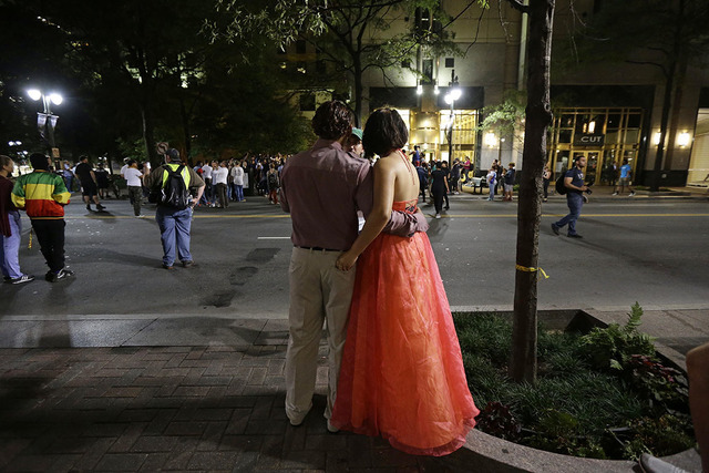 A couple watches along Trade Street in uptown as demonstrators take to the streets following Tuesday's police shooting of Keith Lamont Scott in Charlotte, N.C., Thursday, Sept. 22, 2016. (AP Photo ...