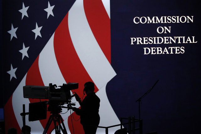 A cameraman is silhouetted against an an American flag during preparations for the presidential debate at Hofstra University in Hempstead, NY, Sunday, Sept. 25, 2016. (AP Photo/Mary Altaffer)