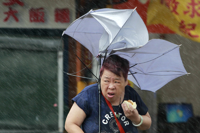 A woman eats and struggles with her umbrella against powerful gusts of wind generated by typhoon Megi across the the island in Taipei, Taiwan, Tuesday, Sept. 27, 2016. Schools and offices have bee ...