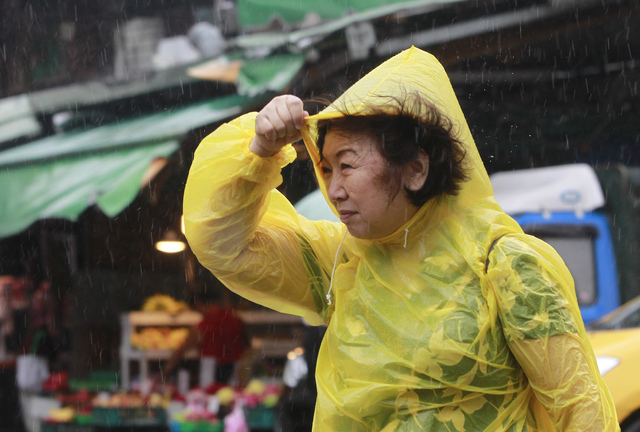 A woman struggles against powerful gusts of wind generated by typhoon Megi across the the island in Taipei, Taiwan, Tuesday, Sept. 27, 2016. (AP Photo/Chiang Ying-ying)