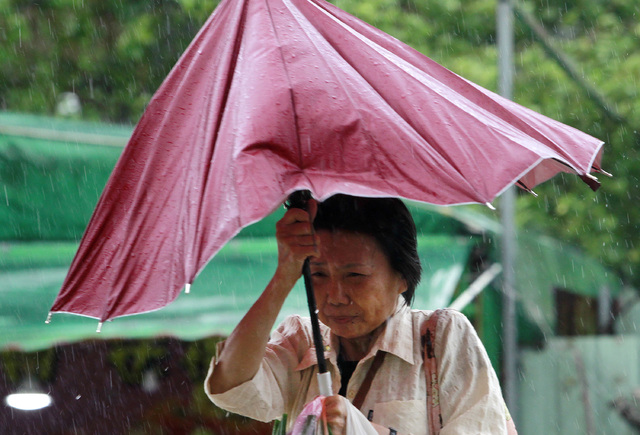 A woman struggles with her umbrella against powerful gusts of wind generated by typhoon Megi across the the island in Taipei, Taiwan, Tuesday, Sept. 27, 2016. (AP Photo/Chiang Ying-ying)