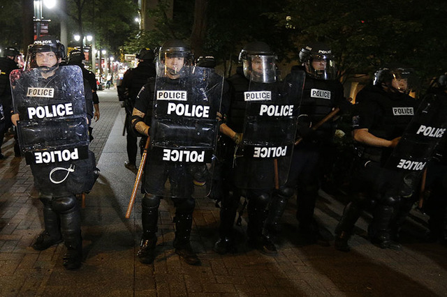 Police officers stand watch after Tuesday's fatal police shooting of Keith Lamont Scott in Charlotte, N.C. Thursday, Sept. 22, 2016. (AP Photo/Chuck Burton)