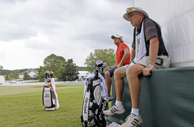 Caddies Dom Thom, right, and Steve Fell wait out a rain delay outside a hospitality suite for players and their caddies during the second round of the Sanderson Farms Championship golf tournament, ...