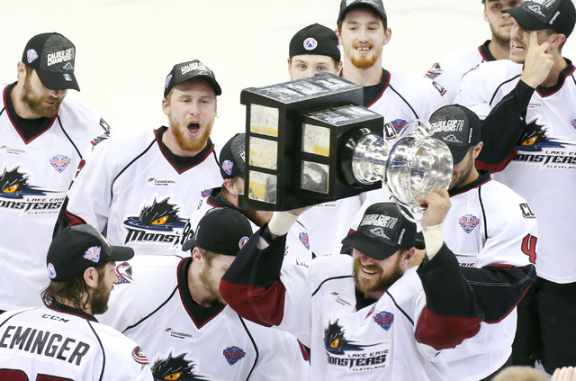Lake Erie Monsters captain Ryan Craig raises the Calder Cup first after the Monsters beat the Hershey Bears 1-0 in overtime in the Calder Cup at Quicken Loans Arena in Cleveland in June. (Chuck Cr ...
