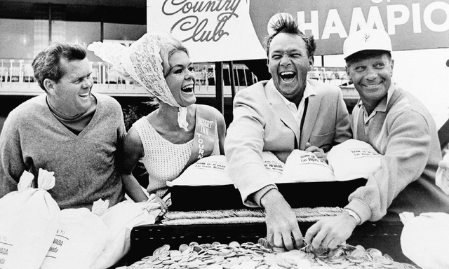 Arnold Palmer, second from right, laughs as he runs his hand through the $20,000 he won by defeating Gary Brewer, left, in a playoff round in the $100,000 Tournament of Champions held at the Deser ...