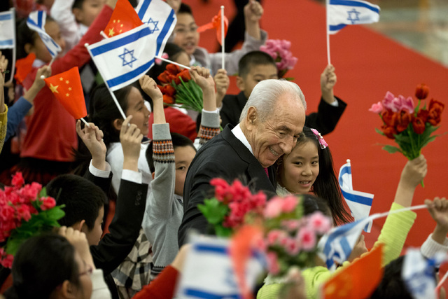 Israeli President Shimon Peres, center, hugs Chinese children during a welcome ceremony held by Chinese president Xi Jinping at the Great Hall of the People in Beijing Tuesday, April 8, 2014. (Ale ...