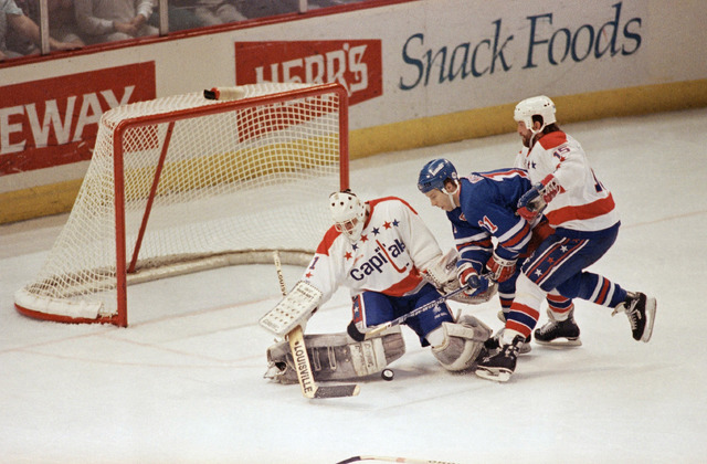 Washington Capitals goalie Mike Liut, left, makes the stop on New York Rangers center Kelly Kisio's shot on goal between the defence of capitals defenseman Neil Sheehy during the second period of  ...