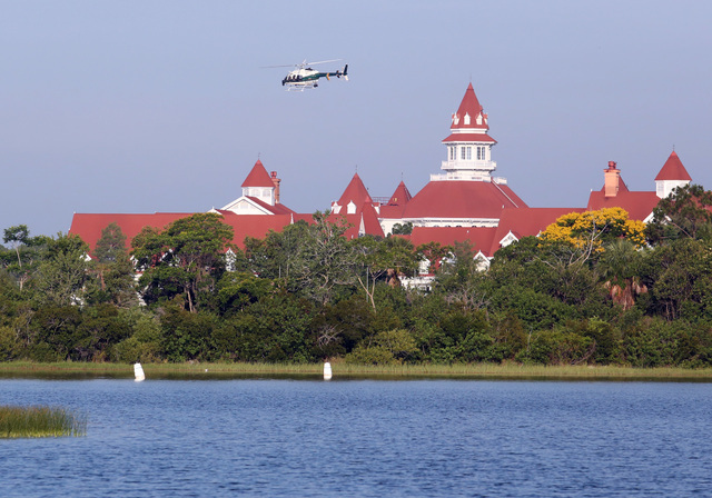 An Orange County Sheriffs helicopter searches for a young boy early Wednesday, June 15, 2016, after the boy was dragged into the water by an alligator near Disney's upscale Grand Floridian Resort  ...