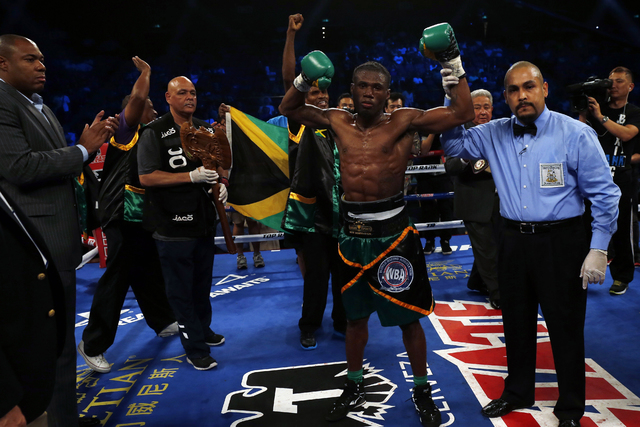 Nicholas The Axe Man Walters of Jamaica, second right, celebrates after winning the WBA World Featherweight Title boxing match against Vic Raging Bull Darchinyan of U.S. in Macau, Saturday, May 31 ...