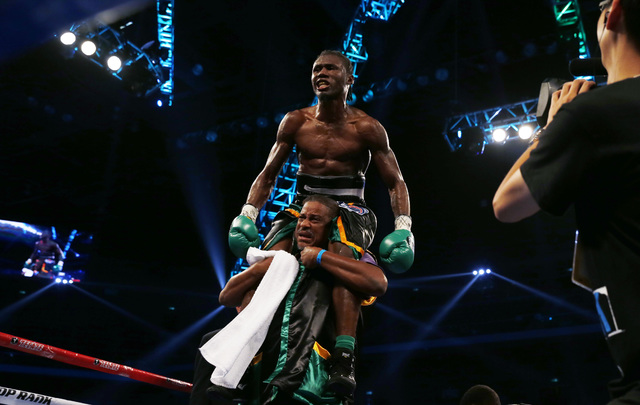 Nicholas The Axe Man Walters of Jamaica celebrates after winning the WBA World Featherweight Title boxing match against Vic Raging Bull Darchinyan of the U.S. in Macau Saturday, May 31, 2014. (Kin ...