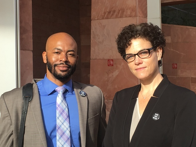 Defense attorneys Jonathan MacArthur and Monique McNeill wear Black Lives Matter pins Wednesday as they stand outside the Regional Justice Center in downtown Las Vegas. (photo by David Ferrara)