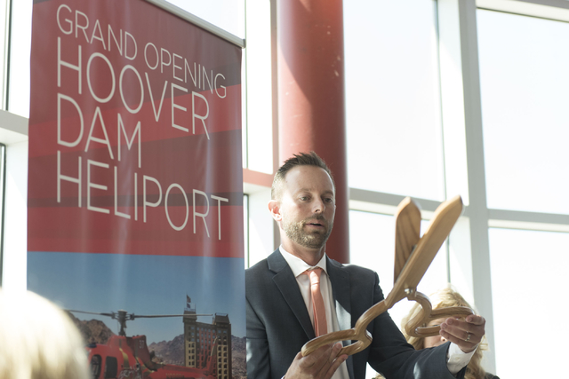 At Boulder City Municipal Airport, Geoff Edlund, president of Papillon Grand Canyon Helicopters, prepares to cut the ribbon during a ceremony for the company's new Hoover Dam heliport in Boulder C ...