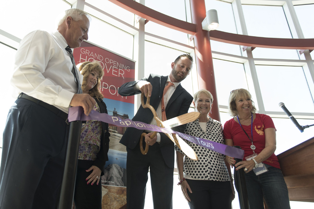 At Boulder City Municipal Airport, Geoff Edlund, president of Papillon Grand Canyon Helicopters, center, cuts the ribbon during a ceremony for the company's new Hoover Dam heliport in Boulder City ...