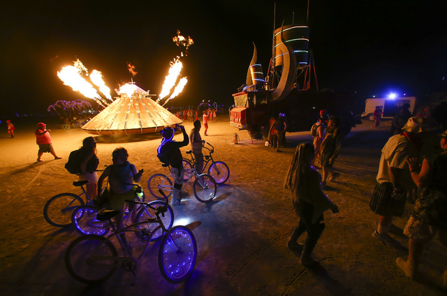 Attendees walk by art cars during Burning Man at the Black Rock Desert north of Reno on Tuesday, Aug. 30, 2016. Chase Stevens/Las Vegas Review-Journal Follow @csstevensphoto