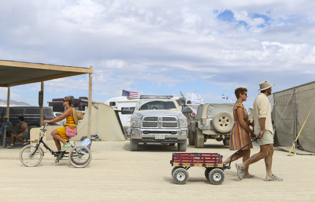 Attendees walk towards the center camp with a cart during Burning Man at the Black Rock Desert north of Reno on Wednesday, Aug. 31, 2016. Chase Stevens/Las Vegas Review-Journal Follow @csstevensphoto