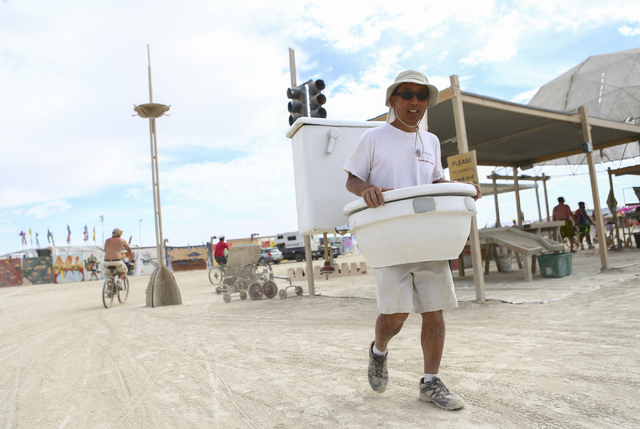 "Gordon Hamachi walks around dressed as a toilet during Burning Man at the Black Rock Desert north of Reno on Wednesday, Aug. 31, 2016. He started dressing as a toilet because it is ""somet ..."