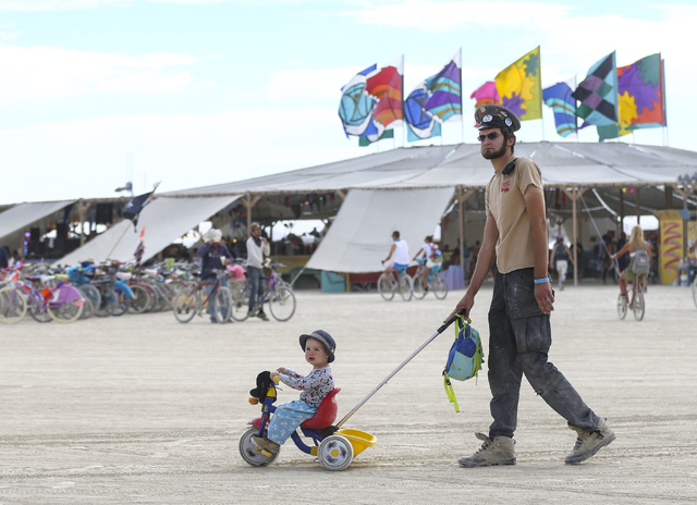 A man pushes a small child around during Burning Man at the Black Rock Desert north of Reno on Wednesday, Aug. 31, 2016. Chase Stevens/Las Vegas Review-Journal Follow @csstevensphoto