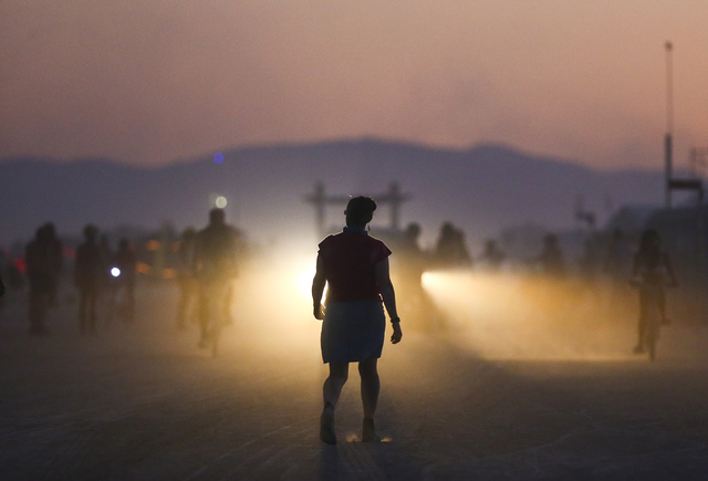 An attendee is silhouetted by the lights of a vehicle during Burning Man at the Black Rock Desert north of Reno on Wednesday, Aug. 31, 2016. Chase Stevens/Las Vegas Review-Journal Follow @cssteven ...