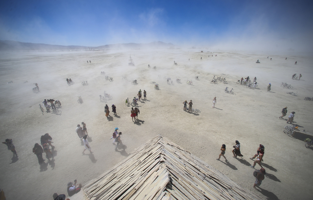 Attendees approach the Catacomb of Veils art installation as dust kicks up along the playa during Burning Man at the Black Rock Desert north of Reno on Thursday, Sept. 1, 2016. Chase Stevens/Las V ...