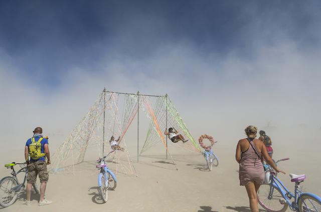 People swing on an art installation during Burning Man at the Black Rock Desert north of Reno on Thursday, Sept. 1, 2016. Chase Stevens/Las Vegas Review-Journal Follow @csstevensphoto