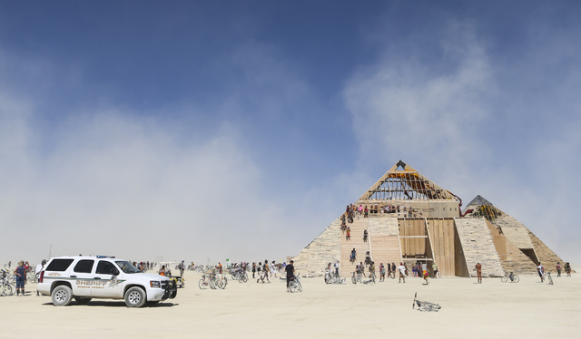A Washoe County Sheriff vehicle sits on the playa as attendees explore the Catacomb of Veils art installation during Burning Man at the Black Rock Desert north of Reno on Thursday, Sept. 1, 2016.  ...