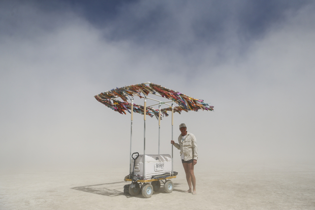 Babba, his playa name, of Bishop, Calif., stands with his cart where he gives out beer and water on the playa during Burning Man at the Black Rock Desert north of Reno on Thursday, Sept. 1, 2016.  ...