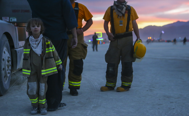 Sagan Bocskor, 5, who created the art installation Jedi Dog Temple, hides behind his dad, Leslie, before the burning of his art piece during Burning Man at the Black Rock Desert north of Reno on T ...