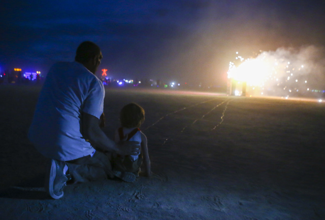 "Pyrotechnician Eric Rebollo, or Big E, his playa name, helps Sagan Bocskor, 5, set his art piece ""Jedi Dog Temple"" to burn during Burning Man at the Black Rock Desert north of Reno on Thursday, Se ..."