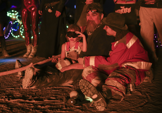 Five-year-old Sagan Bocskor watches his art piece Jedi Dog Temple burn with his dad, Leslie, and mother, Cory Mervis-Bocskor, during Burning Man at the Black Rock Desert north of Reno on Thursday, ...