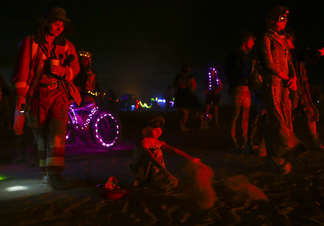 Five-year-old Sagan Bocskor, center, throws up sand as his art piece Jedi Dog Temple burns during Burning Man at the Black Rock Desert north of Reno on Thursday, Sept. 1, 2016. (Chase Stevens/Las  ...