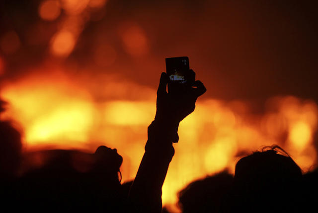 An attendee takes a photo as the Man burns during Burning Man at the Black Rock Desert north of Reno on Saturday, Sept. 3, 2016. Chase Stevens/Las Vegas Review-Journal Follow @csstevensphoto