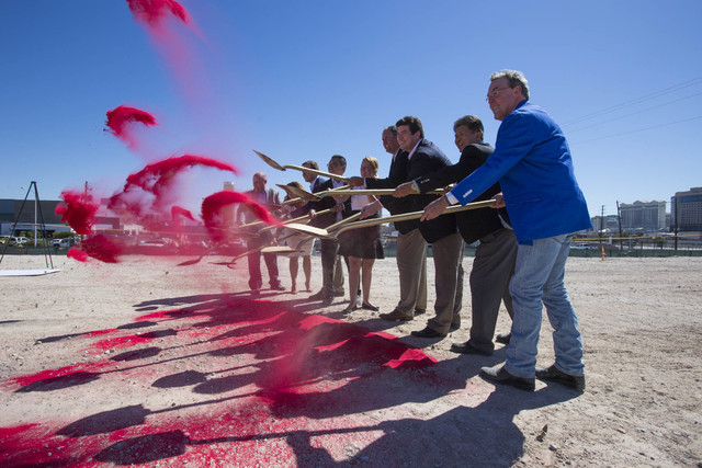 Officials from the Fore Property Company, Argosy Real Estate Partner's and other dignitaries shovel red-colored sand on Monday, Sept. 26, 2016, during a groundbreaking ceremony for a luxury apartm ...