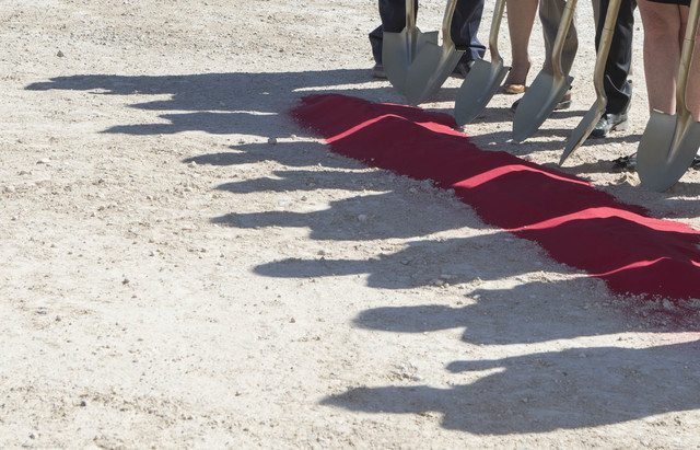 Officials from the Fore Property Company, Argosy Real Estate Partner's and other dignitaries cast shadows on Monday, Sept. 26, 2016, as they prepare to shovel red-colored sand during a groundbreak ...